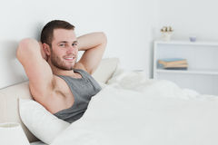 Smiling man waking up. In his bedroom Stock Images