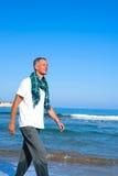 Smiling man  walking along beach Stock Photography