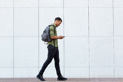 Smiling man walking with backpack smart phone and headphones. Full length side portrait of smiling man walking with backpack smart phone and headphones Royalty Free Stock Photo