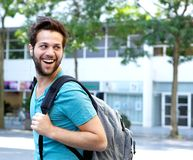 Smiling man walking with bag outdoors Stock Photo
