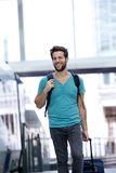 Smiling man walking with bags at train station Royalty Free Stock Photos