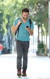 Smiling man walking in the city with mobile phone and bag Royalty Free Stock Photography