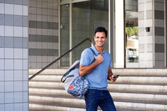Smiling man walking in city with mobile phone and bag Royalty Free Stock Photos