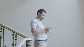 Smiling man walking down the stairs stock footage
