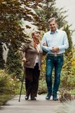 Smiling man walking with happy elderly woman stock photography