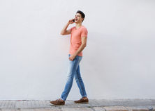 Smiling man walking and listening to mobile phone Stock Photo