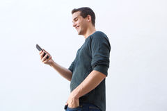 Smiling man walking and looking at mobile phone Stock Photography