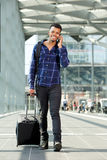 Smiling man walking with suitcase talking on mobile phone Stock Images