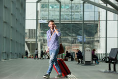 Smiling man walking in the train station with a phone Royalty Free Stock Photography