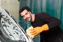 A smiling man washes a mirror of a car royalty free stock photos