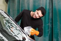 A smiling man washes a mirror of a car royalty free stock photo