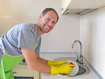 Smiling man washing dish Stock Photography