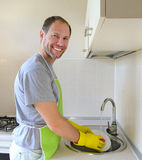 Smiling man washing dish in the kitchen Stock Images
