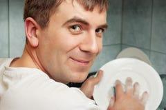 Smiling man washing dish Royalty Free Stock Photo