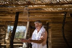 Man washing hands from shower in cottage during safari vacation Stock Image