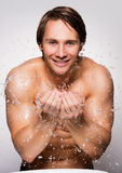 Smiling man washing his healthy face with water. Stock Photography