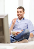 Smiling man watching sports at home Stock Photography