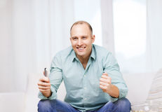 Smiling man watching sports at home Royalty Free Stock Images