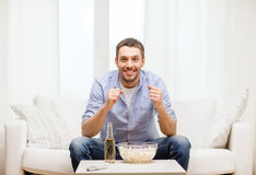 Smiling man watching sports at home Royalty Free Stock Photo