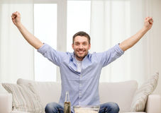 Smiling man watching sports at home Stock Photo