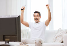 Smiling man watching sports at home Stock Photos