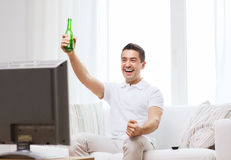 Smiling man watching tv and drinking beer at home Royalty Free Stock Image