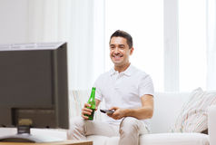 Smiling man watching tv and drinking beer at home Royalty Free Stock Images