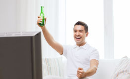 Smiling man watching tv and drinking beer at home Stock Photography