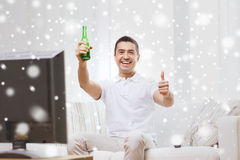 Smiling man watching tv and drinking beer at home Stock Photo