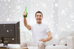Smiling man watching tv and drinking beer at home Royalty Free Stock Photos