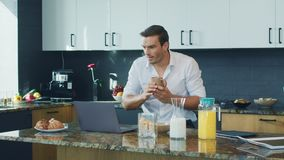 Smiling man watching video standing in kitchen. Happy person scrolling computer. Smiling man watching video standing in big kitchen. Happy male professional stock footage