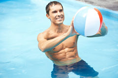 Smiling man with water ball in pool Royalty Free Stock Photography