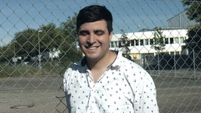 A Smiling Man Waves at the Camera. A man waves at the camera and has a big smile on his face. He stands behind a wire fence on a bright sunny day stock video footage