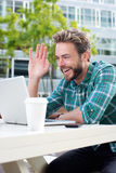 Smiling man waving hello on chat with laptop Stock Images