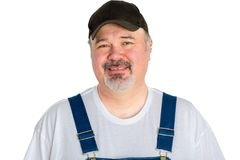 Smiling man wearing cap with dungarees. Portrait of cheerful man wearing cap with dungarees against white background Royalty Free Stock Photo