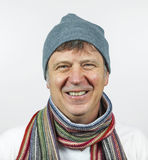 Smiling man wearing a cap and a scarf isolated on a white background Stock Photo