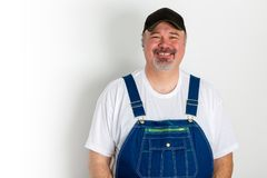 Smiling man wearing dungarees with cap. Portrait of mature cheerful man wearing dungarees with cap against white background Stock Photos