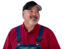 Smiling man wearing dungarees on white background. Cheerful male worker wearing dungarees standing against white background Royalty Free Stock Image