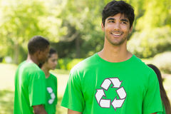 Smiling man wearing green recycling t-shirt in park Stock Photo