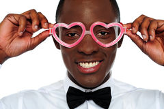 Smiling man wearing heart shaped eye-wear Royalty Free Stock Photography