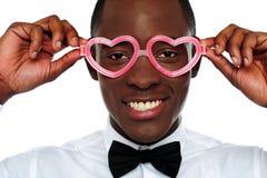 Smiling man wearing heart shaped eye-wear Royalty Free Stock Photography