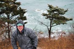 Smiling man wearing O2 rainwear outdoors. Guy in grey O2 brand rain jacket climbs winter hill in blowing rain and wind. Blue green azure ocean with rocky beach stock photo