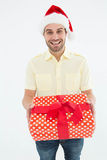 Smiling man wearing Santa hat while holding gift Royalty Free Stock Image