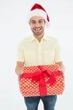 Smiling man wearing Santa hat while holding gift. Portrait of smiling man wearing Santa hat while holding gift on white background Royalty Free Stock Image