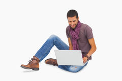 Smiling man wearing scarf sitting on floor using laptop Royalty Free Stock Photos