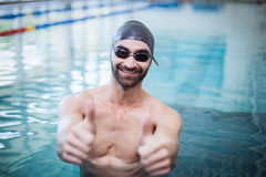 Smiling man wearing swim cap and goggles with thumbs up. At the pool Royalty Free Stock Images