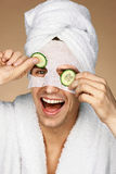 Smiling man wears cotton mask and holding slices of cucumbers. Photo of man enjoying a facial treatment. Beauty & Skin care concept Stock Photography