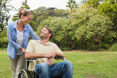 Smiling man in wheelchair talking with partner Stock Images