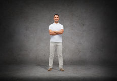Smiling man in white t-shirt with crossed arms Stock Photo