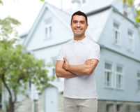 Smiling man in white t-shirt over house background Royalty Free Stock Photos